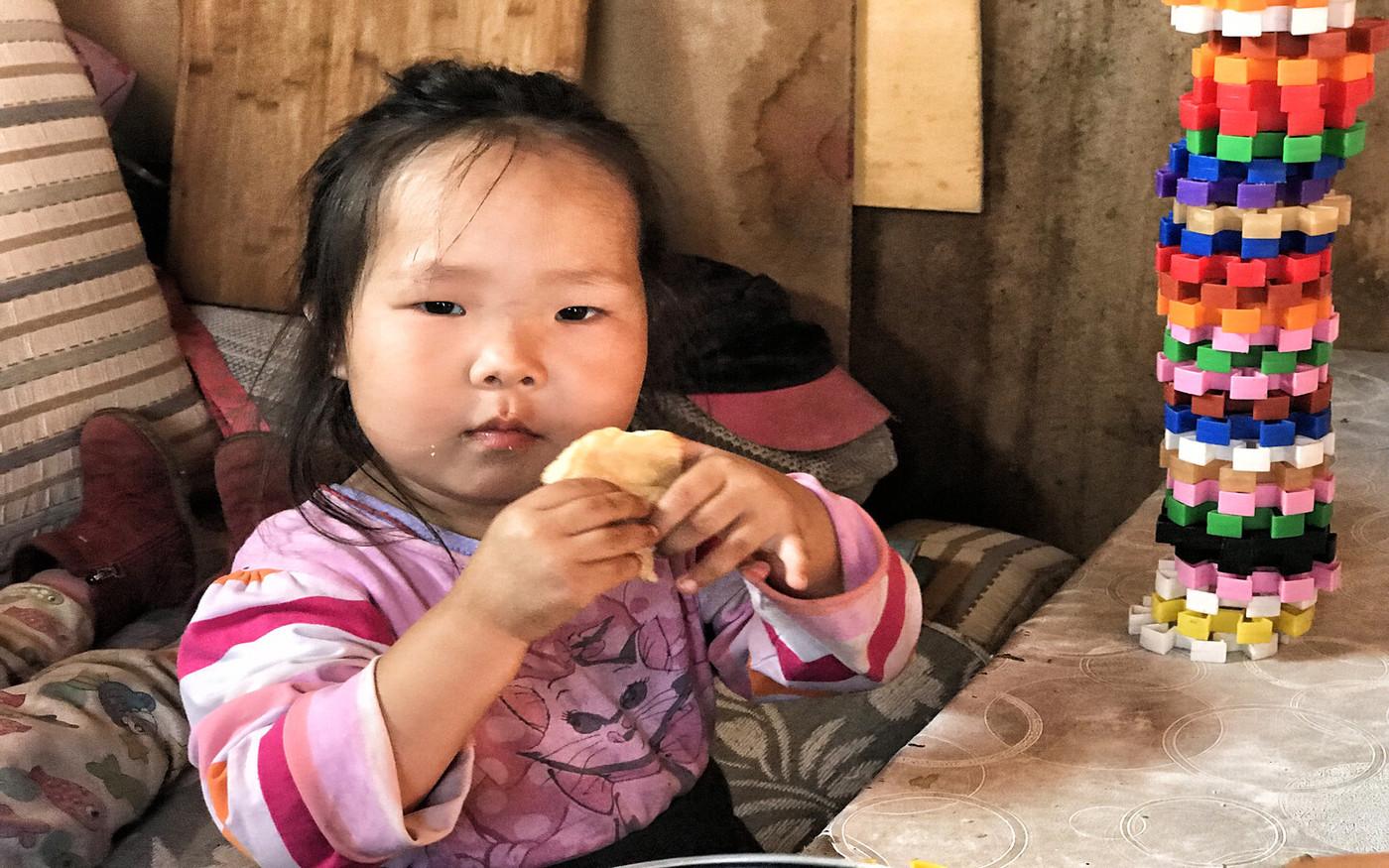 Ein mongolisches Mädchen beim Essen